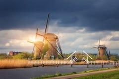 Molinoes de viento contra el cielo nublado en la puesta del sol en Kinderdijk, Netherland Foto de archivo
