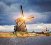 Molinoes de viento contra el cielo nublado en la puesta del sol en Kinderdijk, Netherland Fotografía de archivo libre de regalías