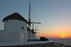 Molinoes de viento de Mykonos en la puesta del sol Imagen de archivo libre de regalías