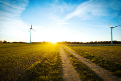 Molinoes de viento en el campo en la puesta del sol Foto de archivo libre de regalías