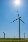 Molinoes de viento en el campo, sol en cielo azul Fotografía de archivo