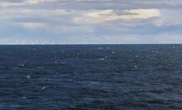 Molinoes de viento en el horizont que rodea por el mar Foto de archivo