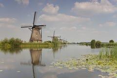 Molinoes de viento en el río Foto de archivo