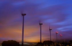 Molinoes de viento en la noche Imagenes de archivo