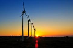 Molinoes de viento en la puesta del sol Imagenes de archivo