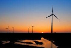 Molinoes de viento en la puesta del sol Imágenes de archivo libres de regalías