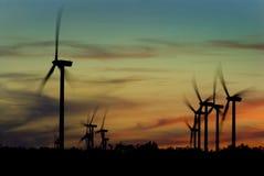 Molinoes de viento en la puesta del sol Imagen de archivo