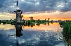 Molinoes de viento en la puesta del sol y la reflexión en agua Foto de archivo libre de regalías