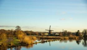 Molinoes de viento a lo largo del lado un río Fotos de archivo libres de regalías