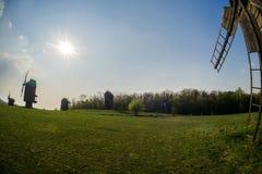 Molinoes de viento de madera en el medio del campo contra la perspectiva del Lem y del cielo con el sol foto de archivo libre de regalías