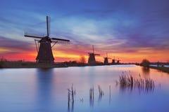 Molinoes de viento tradicionales en la salida del sol, Kinderdijk, los Países Bajos
