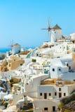 Molinoes de viento y apartamentos en la ciudad de Oia, Santorini Fotografía de archivo libre de regalías