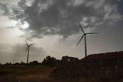 Molinoes de viento y casa vieja en campo fotografía de archivo libre de regalías