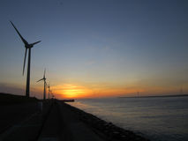 Molinoes de viento y puesta del sol en la playa en Lugang Taiwán Fotografía de archivo libre de regalías