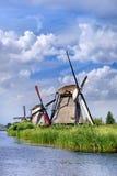 Molinos de viento antiguos cerca de un canal azul en un día de verano hermoso en Kinderdijk, Holanda imagenes de archivo