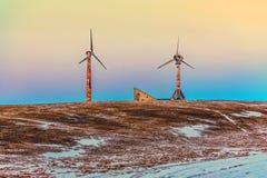 Molinos de viento viejos y oxidados en una montaña de la nieve Fotos de archivo libres de regalías