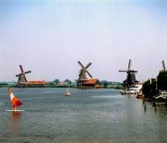 Molinos de viento y persona que practica surf del viento en Zaandam, Países Bajos imagen de archivo