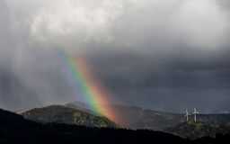 Molinos del arco iris y de la energía eólica en bosque negro Fotos de archivo libres de regalías