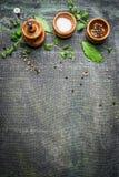 Molinos determinados de las especias, de la sal y de pimienta de la tabla en el fondo rústico, visión superior fotografía de archivo