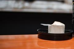 Molkeproteinpulver trägt Bodybuildingergänzung zur Schau Vorderansicht der weißen Schaufel mit Vanillearomapulver auf Holztisch lizenzfreie stockfotos