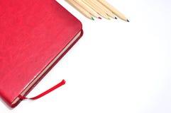 Molkerei, Notizbuch und Bleistifte auf weißem Bürohintergrund Stockfotos
