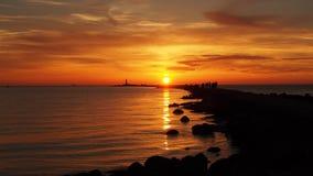 Moll y nubes del mar en la puesta del sol anaranjada Fotos de archivo