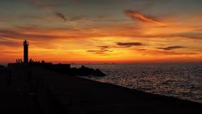 Moll y nubes del mar en la puesta del sol anaranjada Imagen de archivo