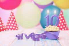 Mollete con la vela del cumpleaños para el décimo cumpleaños Imagen de archivo libre de regalías