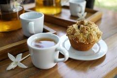 Mollete con una taza de té en la tabla de madera en el jardín Fotos de archivo libres de regalías
