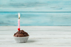 Mollete del chocolate con la vela en la tabla de madera contra fondo azul Fotografía de archivo libre de regalías