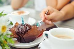 Mollete del chocolate con una vela, tazas con café en etiqueta de madera Imágenes de archivo libres de regalías