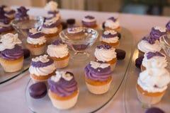 Molletes con la crema, casandose la tabla dulce Magdalenas púrpuras Conjunto de magdalenas Molletes poner crema coloridos Foto de archivo