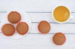Molletes de la galleta en una placa y una taza blancas de té verde En el fondo de madera blanco fotografía de archivo