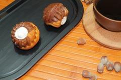 Molletes de la vainilla y del chocolate con una taza de café, de nueces, y de canela Fotos de archivo