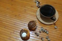 Molletes de la vainilla y del chocolate con una taza de café, de nueces, y de canela Imagenes de archivo