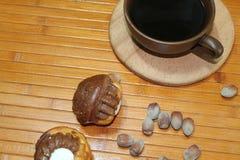 Molletes de la vainilla y del chocolate con una taza de café, de nueces, y de canela Imagen de archivo