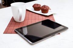 Molletes de los microprocesadores de chocolate con una taza de café y de una tableta Imagen de archivo libre de regalías