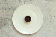 Molletes del chocolate de Brown con el relleno poner crema en una placa blanca en una tabla concreta imagen de archivo libre de regalías