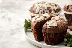 Molletes del chocolate delicioso, dulce, con los pétalos de la almendra al lado de nueces de la menta y de la almendra en una tab foto de archivo