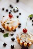 Molletes frescos del arándano, sacados el polvo con el azúcar de formación de hielo y la cereza Imagen de archivo