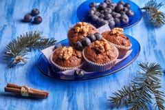 Molletes hechos en casa recién hechos con los arándanos y las nueces en una placa azul en un fondo de madera azul Visión superior imagen de archivo libre de regalías