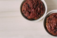 Molletes sanos de las remolachas del vegano en las tazas blancas en backgroun de madera Imagen de archivo