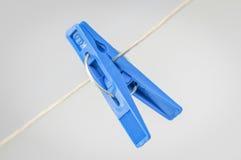 Molletta da bucato che appende su una corda da bucato Fotografia Stock