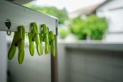 Molletta da bucato verde alta chiusa sullo scaffale d'argento del panno del metallo Fotografie Stock