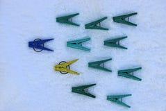 Mollette da bucato colorate fatte della bugia di plastica su neve bianca Fotografia Stock Libera da Diritti