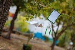 Mollette da bucato su un cavo con permesso bianco e sull'uccello di legno bianco su uno sfondo naturale Fotografie Stock Libere da Diritti
