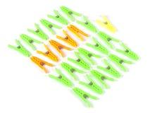 Mollette da bucato variopinte in una fila su fondo bianco Fotografia Stock