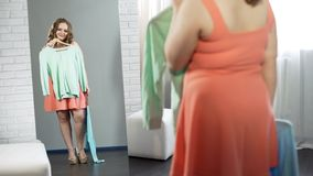Mollig meisje die kleren in kleedkamer, plus groottemanier kiezen, lichaamspositief stock afbeelding