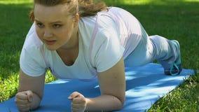 Mollig meisje die plank openlucht, duurzaamheid en sterkte, gezonde levensstijl doen stock video