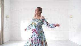 Mollig meisje in het mooie dresse stellen in heldere studio Het mollige vrouw stellen in mooie uitrusting stock footage